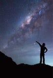Una ragazza sta stando accanto alla galassia della Via Lattea che indica su una stella luminosa Immagine Stock