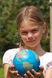 Una ragazza sta tenendo il mondo in sue mani Immagini Stock