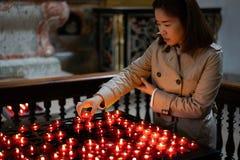 Una ragazza sta tenendo la candela e sta pregando vicino all'altare in chiesa Immagine Stock Libera da Diritti