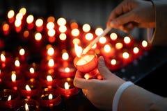 Una ragazza sta tenendo la candela e sta pregando vicino all'altare in chiesa Immagini Stock