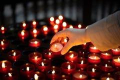 Una ragazza sta tenendo la candela e sta pregando vicino all'altare in chiesa Fotografia Stock