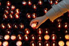 Una ragazza sta tenendo la candela e sta pregando vicino all'altare in chiesa Fotografia Stock Libera da Diritti