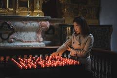 Una ragazza sta tenendo la candela e sta pregando vicino all'altare in chiesa Immagine Stock