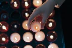 Una ragazza sta tenendo la candela e sta pregando vicino all'altare in chiesa Fotografie Stock
