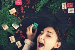 Una ragazza sta tenendo un regalo e sorridere di Natale Fotografie Stock Libere da Diritti
