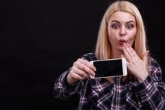 Una ragazza sta tenendo uno smartphone rotto e sta esaminandolo frustratedly Su un fondo nero Primo piano immagini stock