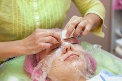 Una ragazza sta trovandosi su uno strato durante le procedure cosmetiche con una maschera sul fronte sopra cui la donna dell'este fotografie stock libere da diritti