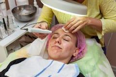 Una ragazza sta trovandosi sullo strato con un cappello rosa sui suoi capelli mentre eseguiva un fronte ultrasonico che pulisce c fotografia stock