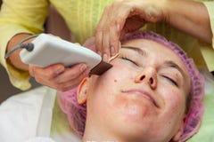Una ragazza sta trovandosi sullo strato con un cappello rosa sui suoi capelli mentre eseguiva un fronte ultrasonico che pulisce c fotografie stock