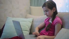 Una ragazza sul sofà è istruzione su un computer portatile video d archivio