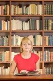 Una ragazza sveglia in biblioteca con il libro aperto che esamina macchina fotografica Fotografia Stock Libera da Diritti