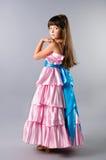 Una ragazza sveglia che propone in un vestito da colore rosa di promenade in studio Immagini Stock