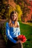 Una ragazza sveglia su una passeggiata in un parco di autunno immagine stock