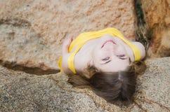 Una ragazza sveglia in un vestito giallo cerca e sorride Immagine Stock