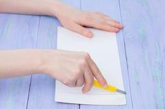 Una ragazza taglia il cartone con un coltello della cancelleria su un fondo di legno porpora fotografie stock libere da diritti