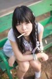 Una ragazza tailandese asiatica sveglia sta sedendosi sul banco con un bastone nella h Immagine Stock