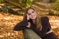 una ragazza teenager di 13 anni nel fogliame di caduta. Fotografia Stock