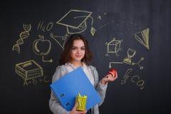 Una ragazza, tenente una cartella, cancelleria e una mela, stante accanto al bordo con un'immagine di scienza Fotografia Stock Libera da Diritti