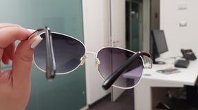 Una ragazza tiene gli occhiali da sole alla moda in sua mano e le vede attraverso una stanza vuota dell'ufficio fotografia stock libera da diritti