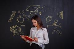 Una ragazza tiene legge un libro rosso aperto, stante accanto ad una placca che descrive i segni di scienza Immagine Stock