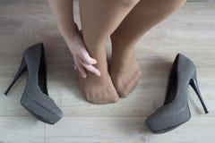 Una ragazza tiene sulla sua gamba, affaticamento dai suoi talloni modella immagini stock