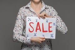 Una ragazza tiene un foglio di carta in mani con un'iscrizione della a Fotografia Stock