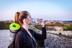 Una ragazza turistica beve l'acqua alla luce solare luminosa fotografia stock