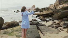 Una ragazza in un abito blu cammina lungo la spiaggia, mette sopra un cappello vietnamita e sorride archivi video