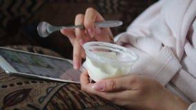 Una ragazza in un accappatoio domestico che si trova sullo strato che funziona con una compressa Allo stesso tempo mangia il yogu stock footage