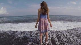 Una ragazza in un bello vestito sta stando sulla costa dell'oceano e sta esaminando la distanza video d archivio