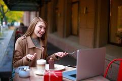 Una ragazza in un caffè all'aperto con un computer portatile che parla con qualcuno via una video chiamata, con gli strumenti in  Fotografie Stock Libere da Diritti