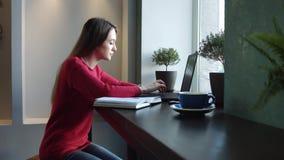Una ragazza in un caffè che lavora ad un computer portatile video d archivio
