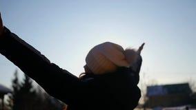 Una ragazza in un cappello bianco è soddisfatta del sole dell'inverno, il tramonto, sollevando le sue mani su, prendendo gli effe stock footage