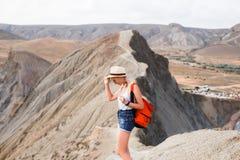 Una ragazza in un cappello di paglia e con uno zaino cammina lungo una cresta della montagna in mezzo al deserto Immagine Stock Libera da Diritti