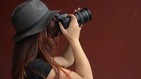 Una ragazza in un cappello fa le foto con una macchina fotografica di DSLR Primo piano video d archivio