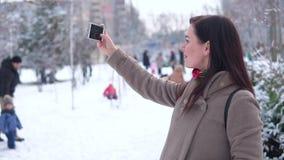 Una ragazza, in un cappotto, facente selfie in un parco di inverno contro un fondo della gente felice video d archivio