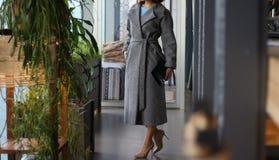 Una ragazza in un cappotto grigio e nelle scarpe beige, con una borsa nera, sta nel corridoio di un caffè, l'hotel, ristorante, v fotografia stock libera da diritti