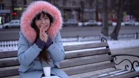 Una ragazza in un cappotto grigio prova a riscaldarla mani congelate nella via nell'inverno stock footage