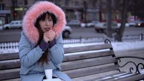 Una ragazza in un cappotto grigio prova a riscaldarla mani congelate nella via nell'inverno video d archivio
