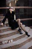 Una ragazza in un cappotto nero Fotografie Stock Libere da Diritti