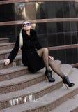 Una ragazza in un cappotto nero Fotografia Stock