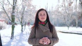 Una ragazza, in un cappotto, passeggia attraverso il parco dell'inverno e beve il caffè mentre esamina la macchina fotografica video d archivio