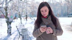 Una ragazza, in un cappotto, passeggia attraverso il parco dell'inverno, scrive un messaggio e beve il caffè stock footage
