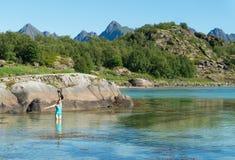 Una ragazza in un costume da bagno con una macchina fotografica nell'acqua del turchese, Lofoten, Norvegia fotografia stock