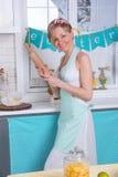 Una ragazza in un grembiule prepara l'alimento Fotografia Stock