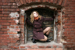 Una ragazza in un incavo del mattone fotografia stock