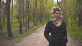 Una ragazza in un rivestimento nero caldo cammina attraverso il legno La ragazza segue la macchina fotografica stock footage