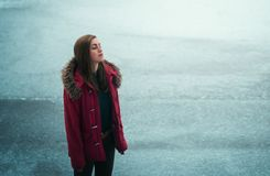 Una ragazza in un rivestimento rosso sta stando su un lago dell'inverno Immagini Stock Libere da Diritti