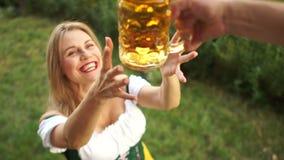 Una ragazza in un vestito bavarese tradizionale compra la birra e la ciambellina salata al festival della birra di Oktoberfest Un video d archivio