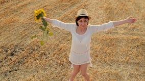 Una ragazza in un vestito bianco ed in un cappello di paglia sta tenendo un mazzo dei fiori da un girasole e restituisce il campo archivi video